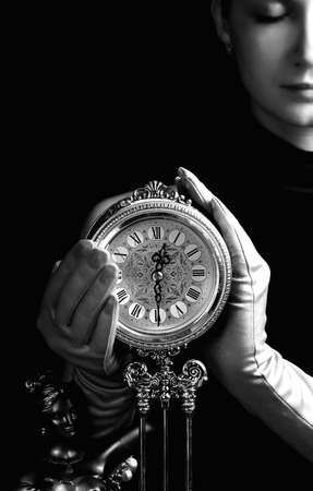 Monochrome picture of a beutiful girl with a clock (focus on clock)