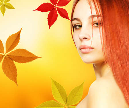 Beautiful young woman over abstract autumn backgroundの写真素材