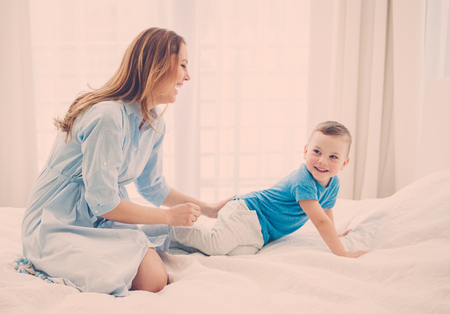 Photo pour Happy middle aged mother with her child in a bed - image libre de droit