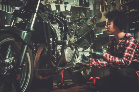 Photo for African american woman mechanic repairing a motorcycle in a workshop - Royalty Free Image