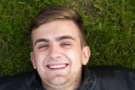 Young adult laying on ground in garden and smiling into the camera.