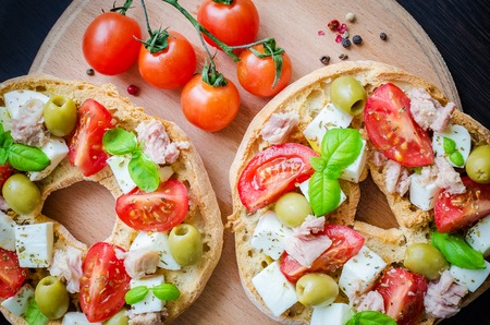 Foto de Classical frisella tomato, cheese mozzarella, tuna and olives. Italian starter friselle. Dried bread called freselle on wooden board with tomatoes cherry. Italian food. Healthy vegetarian food. - Imagen libre de derechos