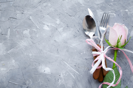 Photo pour Valentine's Day romantic table setting with pastel pink rose and cutlery on grey - image libre de droit