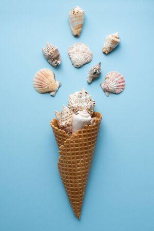 Foto de Creative composition with seashell and ice cream cone on pastel blue - Imagen libre de derechos