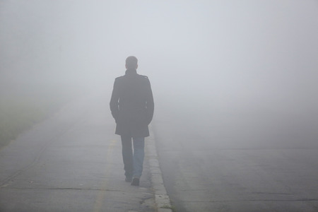 Alone Man from back walking through the fog on street
