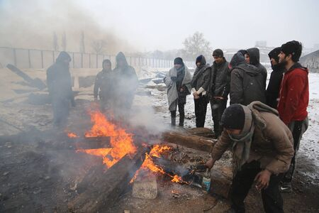 Belgrade, Serbia - January 10, 2017: Migrants warm themselves by the fire in front of an abandoned warehouse in freezing temperatures. Migrant mostly from Afghanistan and Pakistan in Belgrade they seek ways to move on toward Western Europe.
