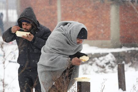 Belgrade, Serbia - January 10, 2017: A migrant eats free food during a snowfall outside a derelict customs warehouse. Migrant mostly from Afghanistan and Pakistan, have occupied an abandoned customs warehouse in Belgrade as they seek ways to move on towar