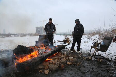 Belgrade, Serbia - January 18, 2017: Refugees warm outside by the fire in an abandoned warehouse in Belgrade. Migrants mostly from Afghanistan and Pakistan in Belgrade they seek ways to move on toward Western Europe.