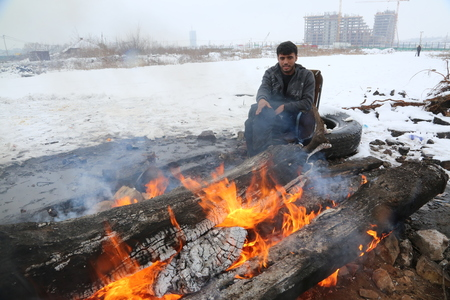Belgrade, Serbia - January 18, 2017: Refugee warm outside by the fire in an abandoned warehouse in Belgrade. Migrants mostly from Afghanistan and Pakistan in Belgrade they seek ways to move on toward Western Europe.
