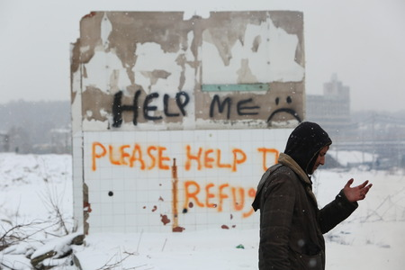 Belgrade, Serbia - January 18, 2017: Refugee standing next to a wall with graffiti for help to refugees in Belgrade, Migrants mostly from Afghanistan and Pakistan in Belgrade they seek ways to move on toward Western Europe.