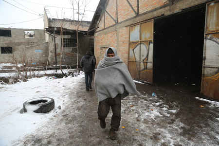 Belgrade, Serbia - January 18, 2017: Refugee with blanket outside in an abandoned warehouse in Belgrade, Migrant mostly from Afghanistan and Pakistan in Belgrade they seek ways to move on toward Western Europe.