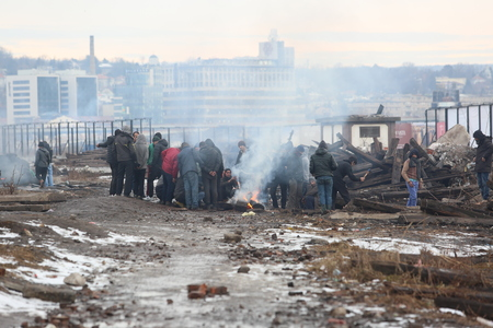 Belgrade, Serbia - January 14, 2017: Refugee heating by the fire outside. Migrant have occupied an abandoned customs warehouse in Belgrade in the way to EU.