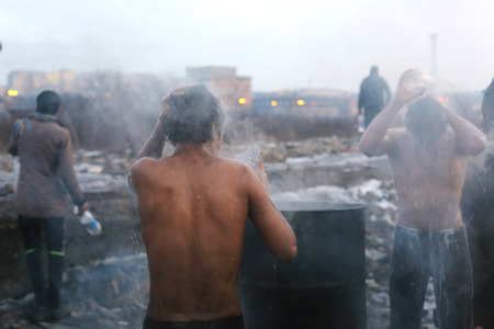 Belgrade, Serbia - January 14, 2017: Refugees washing themselves outside on a cold winter day. Migrant have occupied an abandoned customs warehouse in Belgrade in the way to EU.