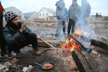 Belgrade, Serbia - January 14, 2017: Refugee cooking lunch by the fire outside. Migrant have occupied an abandoned customs warehouse in Belgrade in the way to EU.