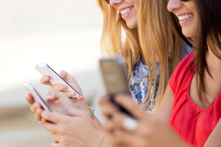 Portrait of three girls chatting with their smartphones at the campus