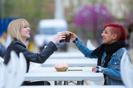 Shot of pretty young women toasting with coke on the street.