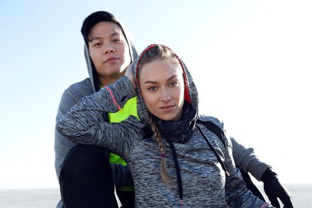Portrait of fit and sporty young couple relaxing after work out in the city.