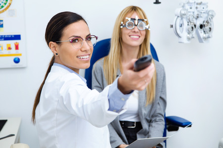 Shot of woman optometrist with trial frame checking patient's vision at eye clinic. Selective focus on doctor.