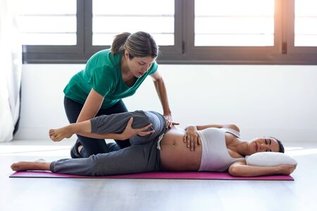 Photo for Shot of physiotherapist helping to beautiful pregnant woman for doing pilates exercises preparing for childbirth. - Royalty Free Image
