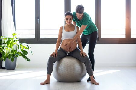 Photo for Shot of physiotherapist helping to beautiful pregnant woman for doing pilates exercises with ball preparing for childbirth. - Royalty Free Image