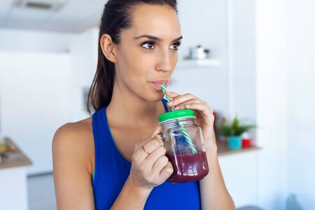 Photo for Shot of beautiful sporty young woman drinking detox juice in the kitchen at home. - Royalty Free Image
