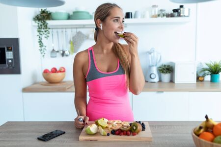 Photo for Shot of pretty young woman eating a piece of apple while listening to music in the kitchen at home. - Royalty Free Image