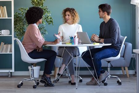 Foto de Shot of casual young business people working and talking of they new project together in the office. - Imagen libre de derechos