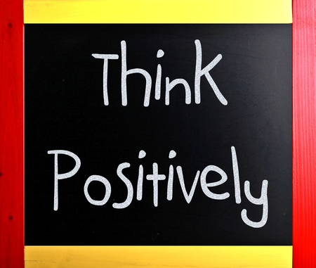 Think Positively handwritten with white chalk on a blackboard