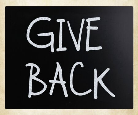 Give back handwritten with white chalk on a blackboard.