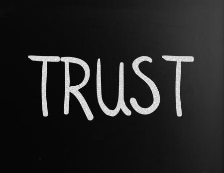 The word Trust handwritten with white chalk on a blackboard