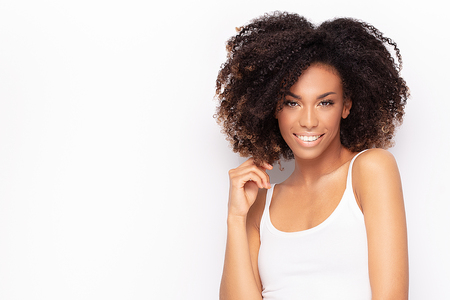 Photo pour Young fashionable afro girl posing in white shirt, smiling to the camera. White studio background. - image libre de droit