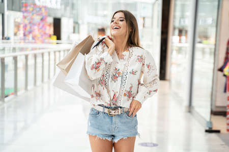 Photo pour Woman with shopping bags walking in shop, smiling. - image libre de droit
