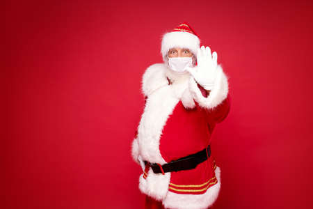 Photo for Real Santa Claus in white mask posing over red studio background. A lot of copy space. - Royalty Free Image