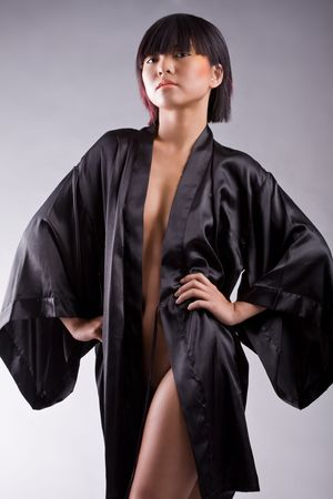 Sexy Asian girl wearing black robe on white studio background