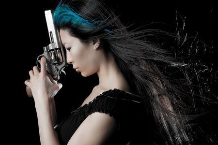 Dangerous Chinese woman with handgun on black studio background