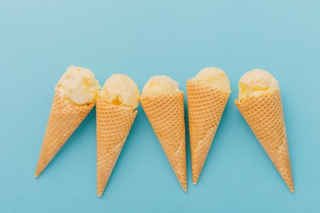 Five delicious ice creams in waffle cones on blue backgroundの写真素材