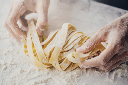 Foto de Closeup of process of making cooking homemade pasta. Chef make fresh italian traditional pasta - Imagen libre de derechos