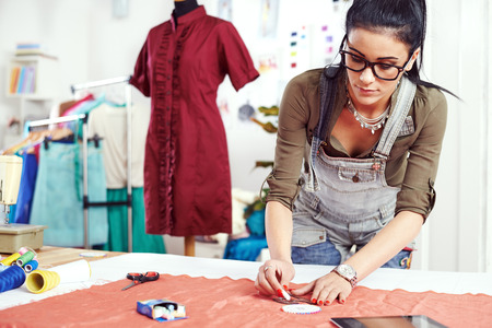 Young female designer drawing on the material