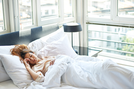 Photo pour Young woman sleeping in bed - image libre de droit