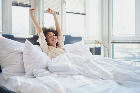 Foto de Young woman stretching in bed - Imagen libre de derechos