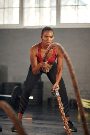 Photo pour Woman working out with ropes in gym - image libre de droit