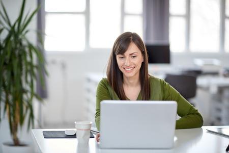 Foto de Beautiful smiling Caucasian businesswoman sitting in modern office and using laptop. - Imagen libre de derechos