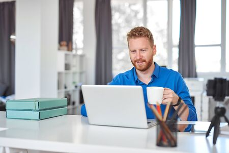 Foto de Young dedicated Caucasian male employee sitting in office, drinking coffee and using laptop. Start up business concept. - Imagen libre de derechos