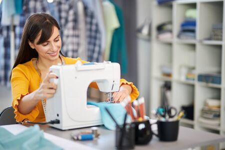 Photo pour Smiling charming caucasian fashion designer sitting in her studio and sewing beautiful evening dress. - image libre de droit