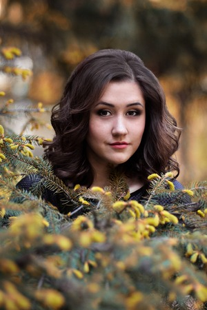 The portrait of beautiful, attractive, cheerful girl, woman, model in the green fir-trees and spruce. Spruce, nature, fir-tree, sunny, happy, portrait, portrait.Very awesome, beautiful, cute girl in the green spring forest and stand near the fir-tree.