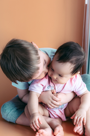Photo pour happy little brother playing hugs his sister baby, boy and girl embraces kisses, concept love and parenting. - image libre de droit