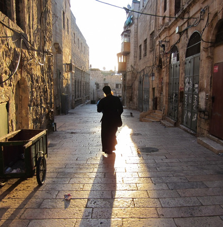 Monk walks down the street to Jerusalem to meet the sunrise