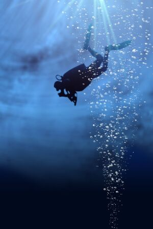 Silhouette of a diver in blue sea