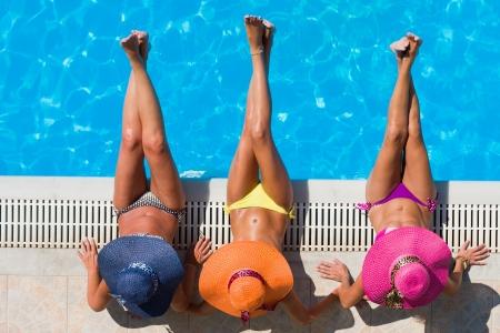 Photo pour Three women in bikini wearing a straw hat by the swimming pool - image libre de droit