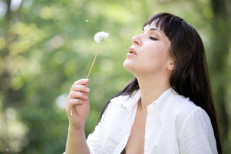 attractive brunette woman with dandelion in park